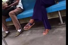 Tan ecumenical crossed legs in flip flops
